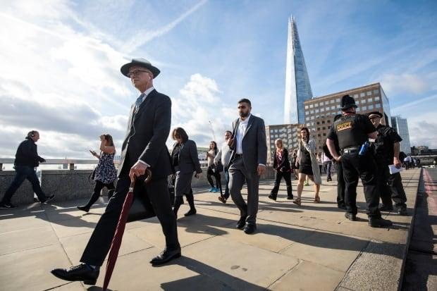 Commuters cross London Bridge following terror attack