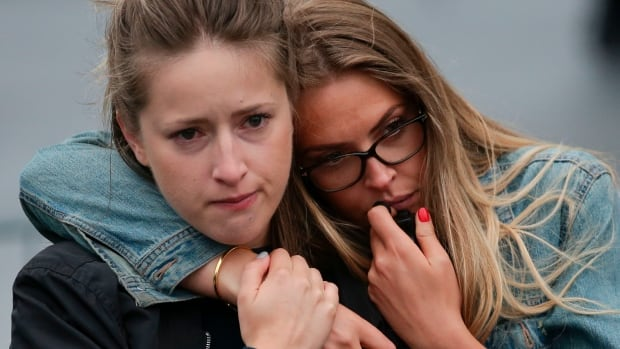 Two women react as they pause at the mound of flowers outside City Hall in London on Monday.