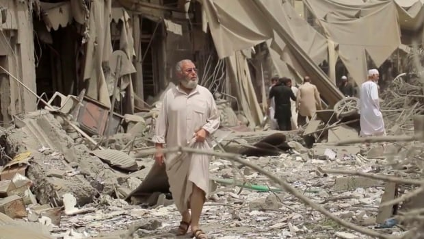 This undated frame grab from video posted online the Aamaq News Agency, a media arm of the Islamic State group, shows people inspecting damage from airstrikes and artillery shelling in the northern Syrian city of Raqqa. Airstrikes began Monday by the U.S. coalition in Syria.