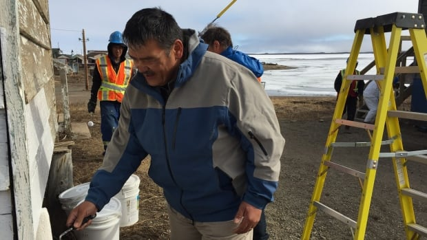 Tuktoyaktuk mayor Darrel Nasogaluak rolls paint onto a building in the hamlet. As the new Inuvik to Tuktoyaktuk Highway inches closer to opening, the community has taken on a two-summer painting project to spruce up buildings in town.
