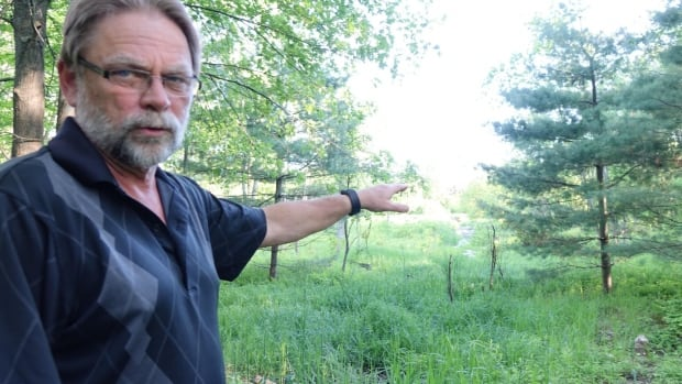 Peter Friske points to the land behind his home on Birchtree Crescent in Navan, where the South Nation Conservation Authority had developed a plan to create a wetland. A meeting held on the divisive issue last week got heated, and the authority has now backed out of the project.