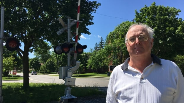 Community organizer Gil Warren stands at the CP tracks on William Street in London, Ont. His home is just 25 metres away.