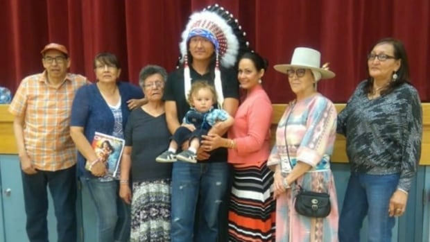 Eugene Brave Rock, centre, is surrounded by family following a ceremony at Tatsikiisaapo'p Middle School in Alberta on Thursday.