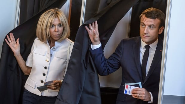 French President Emmanuel Macron, right, and his wife Brigitte Macron leave a polling booth as they vote in the first round of the two-stage legislative elections, in Le Touquet, France, on Sunday.