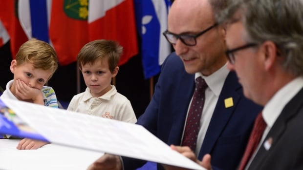 Children look on as Social Development Minister Jean-Yves Duclos and P.E.I. Minister of Education Doug Currie meet with provincial and territorial ministers to sign a multilateral framework on early education and child care.
