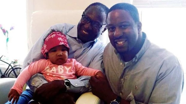 Dr. Joe Galiwango (centre), is shown with his granddaughter Dominique and son Joseph. The popular Windsor, Ont., pediatrician was found dead a year ago and a toxicology report has still not been completed.
