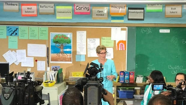 Ontario Premier Kathleen Wynne faces the media as she announces that proceeds from the province's cap and trade program will be used to repair schools across the province.