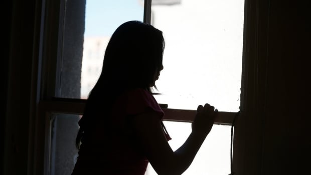 An undocumented woman looks out of a window in Los Angeles. In Montreal, people without documentation continue to face challenges despite a new sanctuary city designation.