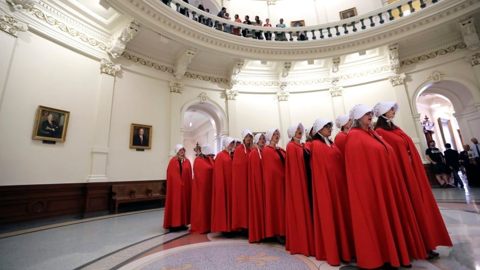 Activists dressed as characters from The Handmaid's Tale chant in the Texas Capitol Rotunda as they protest SB8.