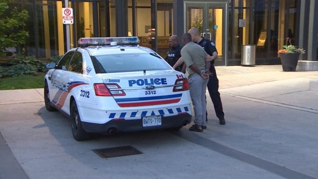 A man is escorted out of a North York, Ont., condo building in the Leslie Street and Sheppard Avenue area as a part of a multi-jurisdictional investigation into the street gang Driftwood Crips.