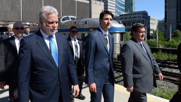 Prime Minister Justin Trudeau, centre, arrives to announce a $1.28-billion commitment toward Montreal's light-rail project alongside Quebec Premier Philippe Couillard, left, and Montreal Mayor Denis Coderre.