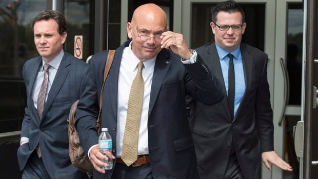 RCMP Commissioner Bob Paulson, centre, heads from the Moncton Law Courts with defence lawyers Ian Carter and Jeff Doody during a break Thursday as he testifies at the RCMP's Labour Code trial in connection with the June 2014 shooting rampage that claimed the lives of three officers.