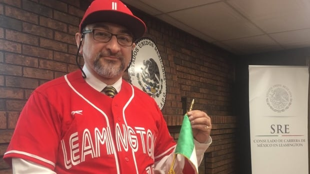 Albert Bernal with the Mexican Consulate wears the jersey for the Mex-Can International Baseball Tournament.