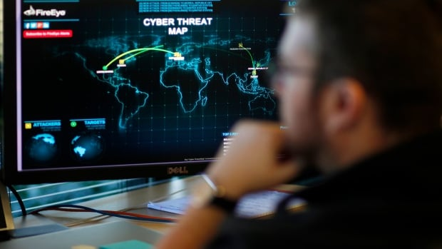 A FireEye information analyst works in front of a screen showing a near real-time map tracking cyber threats at the company office in Milpitas, Calif., in December 2014.