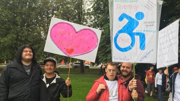 Marchers braved the rains and held up signs with positive messages about disability and diversity.
