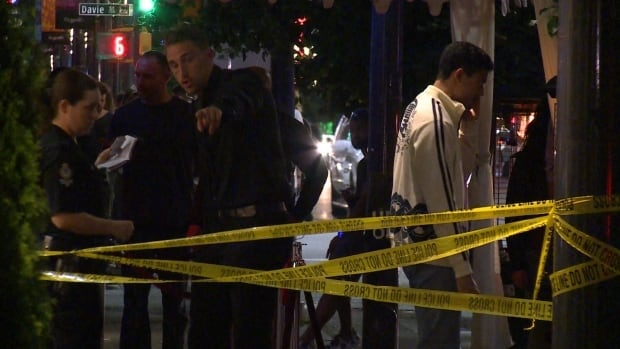 Witness being questioned by Vancouver Police after a man was taken to hospital with stab wounds following a fight on Granville Street last July.