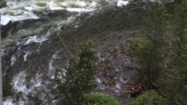 Emergency crews attach a rope to a man pulled out of the Capilano River Thursday evening.