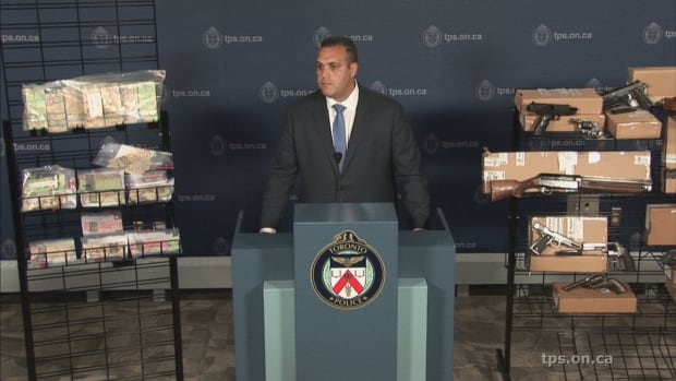 Toronto Police Inspector Peter Moreira shows some of the cash and guns seized in the sweeping 'Project Kronic' raids.