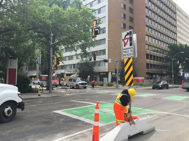 Workers put up the remaining bike lane signs