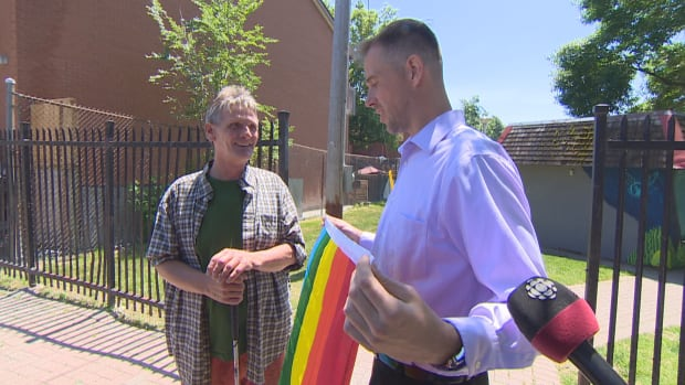 Dean Will, left, receives a new Pride flag from neighbour Michael Rusek after Will's was stolen from his front door.