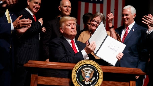 President Donald Trump shows a signed executive order on Cuba policy, Friday, June 16, 2017, in Miami. From left are, Rep, Mario Diaz-Balart, R-Fla., Florida Gov. Rick Scott, Cary Roque, and Vice President Mike Pence.