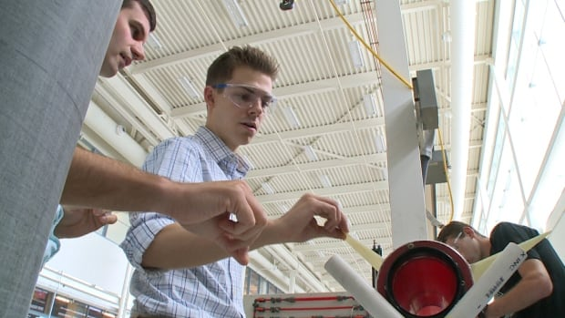 University of Windsor student Patrick Pomerleau-Perron, middle, goes over some final details of a 2.4-metre rocket designed by his team of engineering students, who are heading to New Mexico on Saturday for an international rocketry competition.