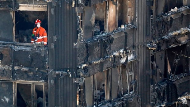 Members of the emergency services work inside the Grenfell Tower block in North Kensington, west London, on Saturday. Police say workers have managed to reach the top of the 24-storey tower.