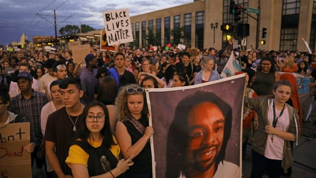 Supporters of Philando Castile hold a portrait of Castile in St. Paul, Minn., leaving a vigil after Jeronimo Yanez was cleared of all charges in the fatal shooting last year of Castile.