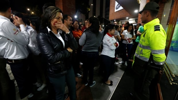 People stand outside the Andino shopping centre in Bogota, Colombia after an explosive device detonated in a restroom, killing three women.