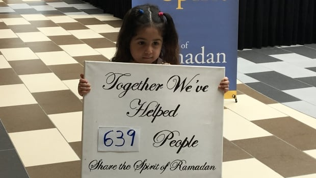 Rital Elassal, 3, holds up a poster at Sunday's Spirit of Ramadan event in Dartmouth, N.S.