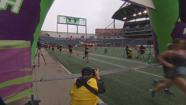 A runner celebrates as she crosses the finish line at Investors Group Field.