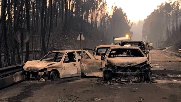 Burned cars are seen on a local road during a forest fire near Pedrogao Grande, Portugal on Sunday. Officials say many people killed in the fire were in their vehicles.