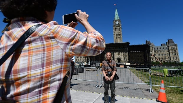Chinese tourists vist Parliament Hill in Ottawa on Wednesday