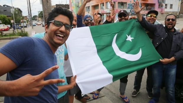 Pakistan fan Hassan Sattar and others celebrate the win in the streets of Toronto on Sunday.