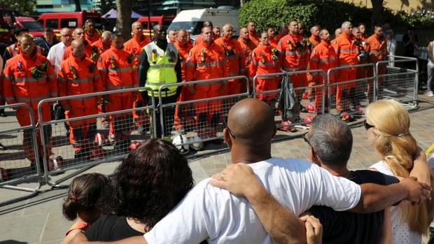 Members of the emergency services join people in a minute's silence for the victims of the Grenfell Tower fire near the site of the blaze in North Kensington, London on Monday.