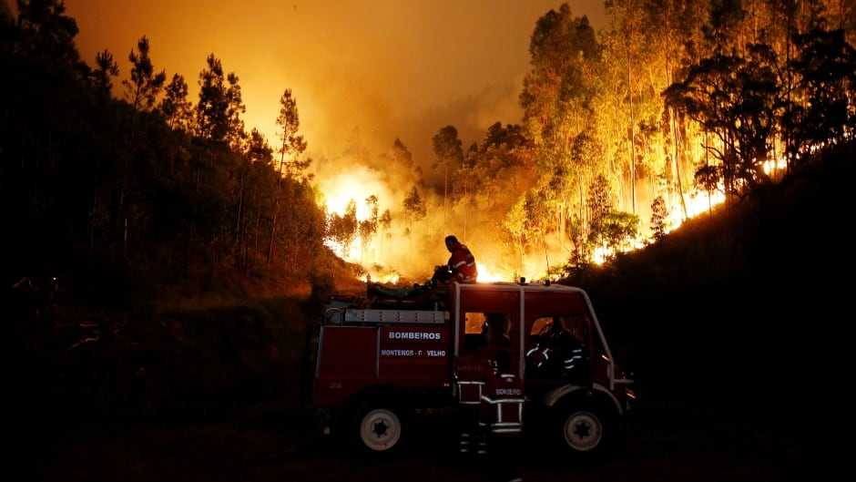 Firefighters work to put out a forest fire near Bouca, in central Portugal. The country is observing three days of national mourning for the dozens killed in the wildfires.