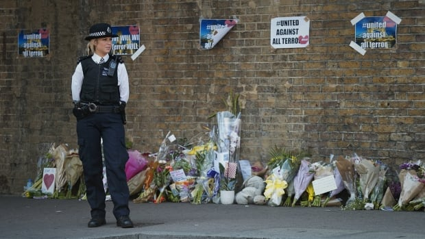 A police officer stands next to a display of flowers near the Finsbury Park mosque in London's north end, where a man drove a van into a crowd early Monday. It was the fourth fatal attack in Britain in as many months.