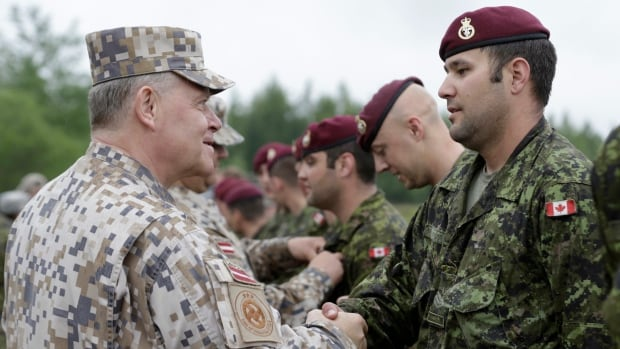 "Latvia's then-chief of defence Raimonds Graube, left, shakes hands with a Canadian paratrooper during the military exercise ""Saber Strike"" in Adazi in 2014. Graube says Russia would be ""absolutely crazy"" to invade while Latvia is playing host to the NATO coalition."