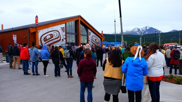 A crowd gathered on Tuesday for the grand opening of the new facility in Carcross, and to watch the totem pole being raised in front of the building.