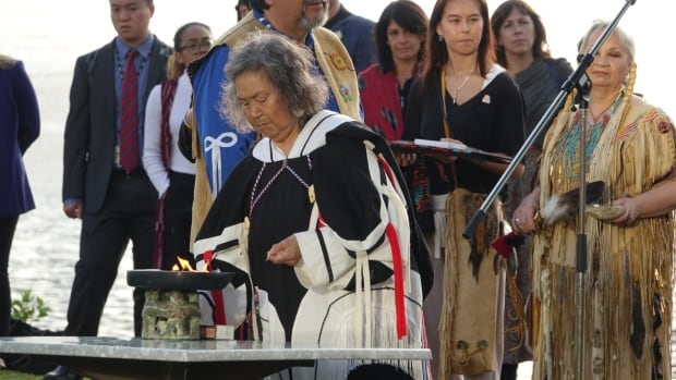Inuk elder Sally Webster lights a kudlik during a summer solstice ceremony on the shore of the Ottawa River behind the Canadian Museum of History in Gatineau to mark National Aboriginal Day.