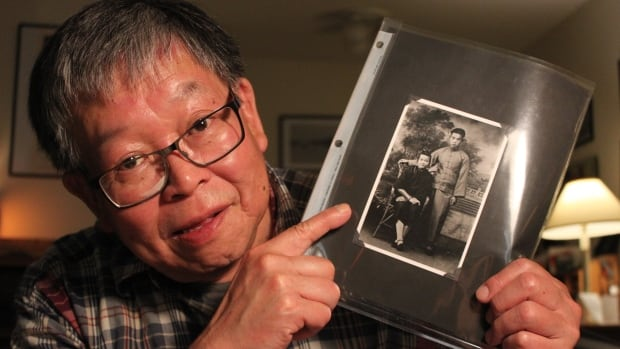 Albert Lee points to his mother and father's wedding photo, one of the few photos of the young couple before they were separated for 14 years.