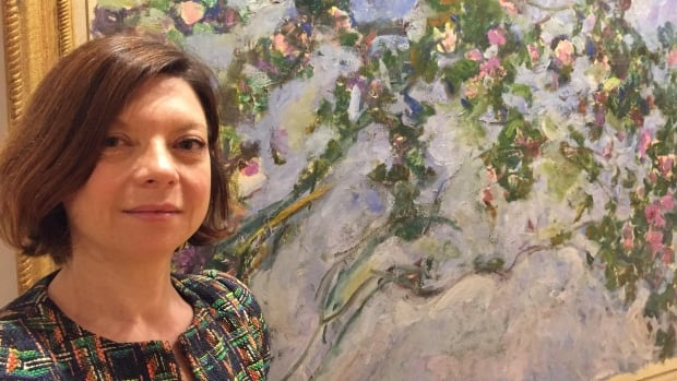 Marianne Matthieu, curator of Claude Monet's Secret Garden, poses with Monet's last painting, Les Roses, at the Vancouver Art Gallery on June 23, 2017.