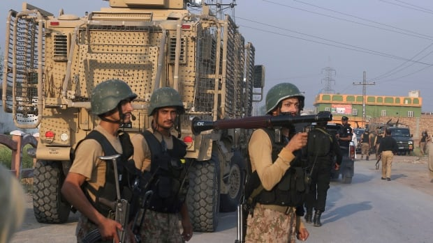 Troops leave after a shootout with militants on the outskirts of Peshawar on Saturday. Security forces raided a militant hideout in the city before dawn, triggering a shootout in which three Pakistani Tailban were killed.