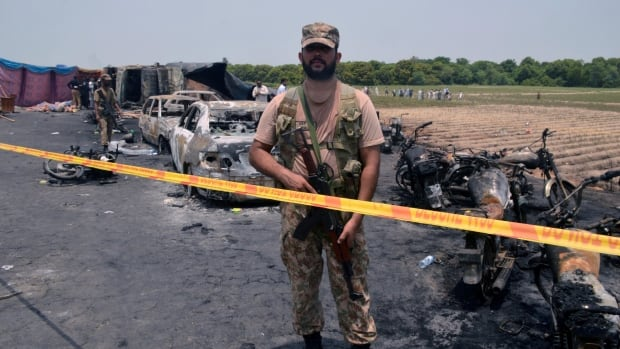 A soldier stands guard at the scene of an oil tanker explosion in Bahawalpur, Pakistan. At least 153 people were killed.
