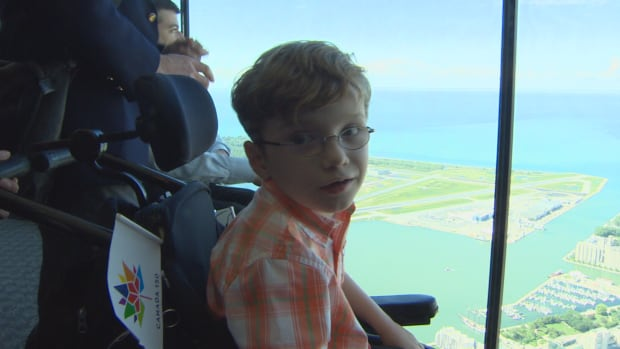 "Zach Rayment enjoys the view of the new floor-to-ceiling windows unveiled today at the CN Tower. He used to have to stand on his wheelchair to see over the metal bar obstructing his view, but Rayment said the new windows ""include all."""