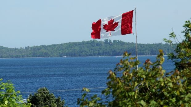 A Canadian flag blows in the breeze. Canada 150 celebrations took place across the country Saturday.