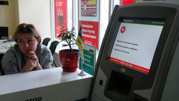 An employee sits next to an out-of-order payment terminal at a Kyiv-based branch of Ukraine's state-owned bank Oschadbank after Ukrainian institutions were hit by a wave of cyberattacks earlier in the day.