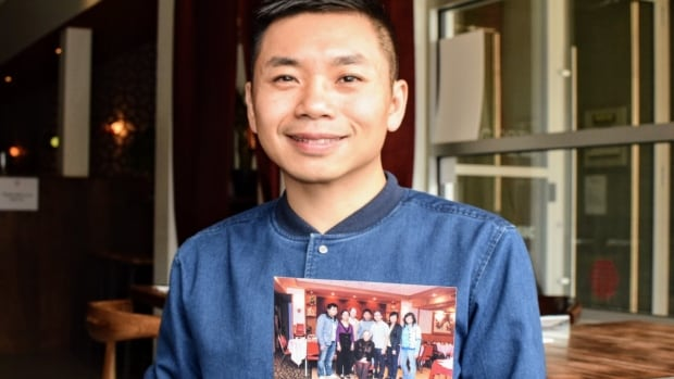 Andy Yuen holds an old family photo from when his parents ran a Chinese restaurant in rural Saskatchewan. Now Yuen works with his parents Jane and Sam and his wife Rachel Kong at the Odd Couple in Saskatoon.