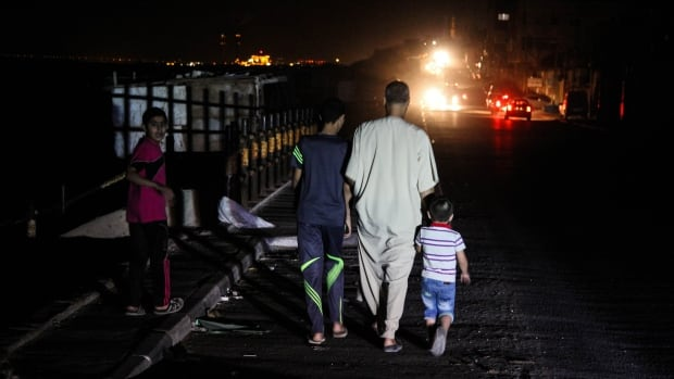A Palestinian family walks through the al-Shati refugee camp in Gaza City. With no power in the area, streets are illuminated only by the headlights of passing vehicles.