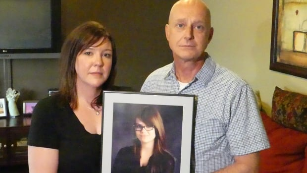 Janet Leflar and her husband, Wade Anderson, hold their daughter Hannah's last school photo.